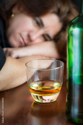 Drunk woman staring at a glass of whiskey