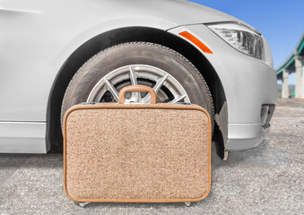 Cloth suitcase and car tire wheel in parking lot