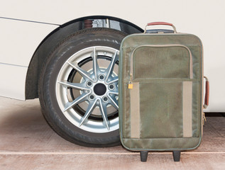 Canvas suitcase and car tire wheel close up