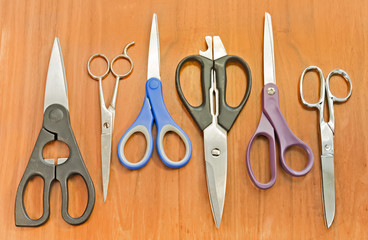 Old assorted scissors in a row on textured wood background