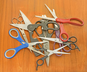 Pile of old assorted scissors on textured wood background