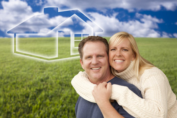 Happy Couple Hugging in Grass Field with Ghosted House Behind