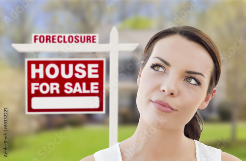 Mixed Race Woman In Front of House and Foreclosure Sign