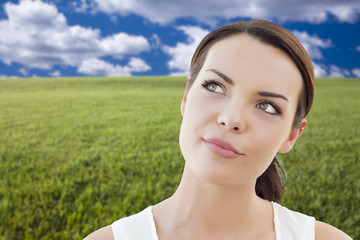 Contemplative Woman in Grass Field Looking Up and Over