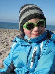 Kind mit Sonnenbrille am Strand im Winter