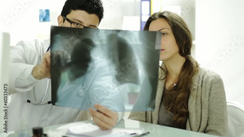 Doctor Explaining Treatment to Young Woman Worried Xray