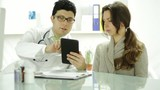 Healthcare Technology Young Doctor Using Tablet to Show Patient