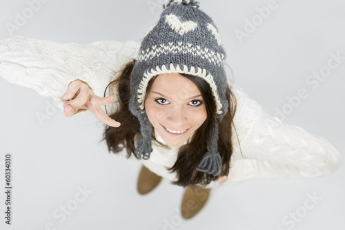 Cute girl in warm winter clothes making victory sign.