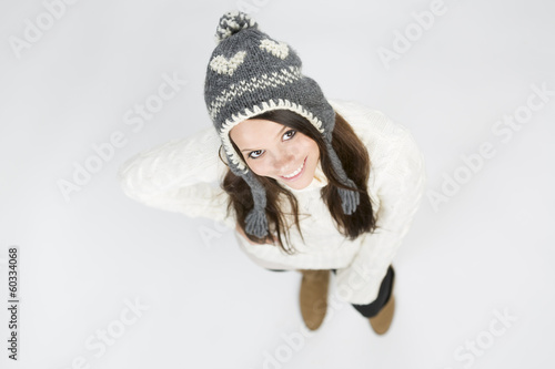 Cute girl in winter clothes looking up and lovely smiling.