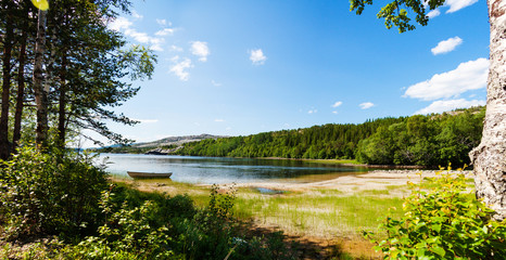 Panoramic view of a lake with boat from a forest in Northern Nor