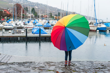 Child under big colorful umbrella watching the rain on the lake