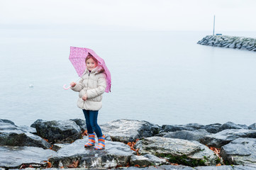 Cute little girl with pink umbrella standing next to lake