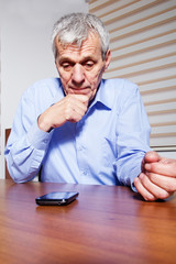 An senior businessman using phone at his office