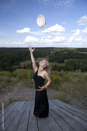 Blonde woman throwing her hat up in the air (swedish landscape)