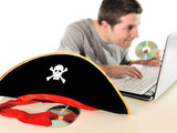Pirate hat and Young man  copying disk with computer