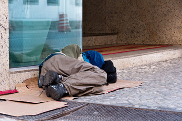 Homeless man sleeping in front of the commercial building
