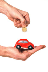 man inserting coin into mini car piggy bank