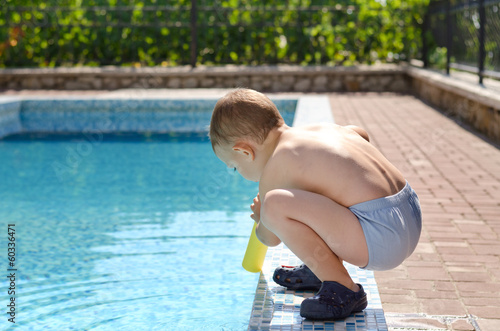 Young boy playing at the edge of a swimming pool