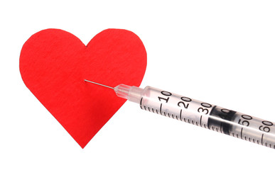 Red heart near a syringe with drug.