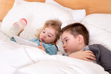 Cute little boy and girl reading before sleeping