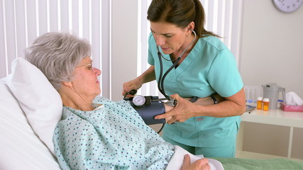 Mature woman nurse checking patient's blood pressure