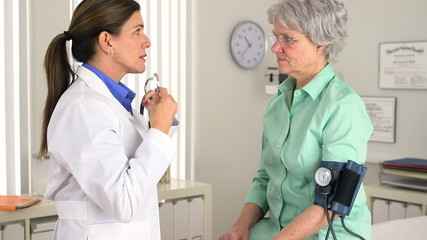 Senior doctor talking to patient while checking blood pressure