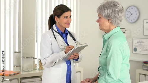 Senior doctor taking notes while talking to patient