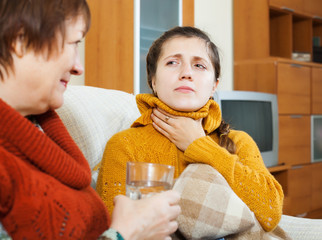 Mature woman caring for sick adult daughter