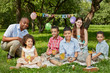 Family of six eats birthday cake sitting on rag matting on grass