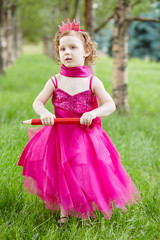 Little girl dressed in bright puffy gown  stands on grassy lawn