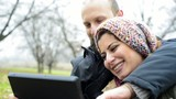 happy lover couple using tablet outdoor in the park winter cold