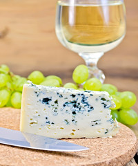 Cheese blue on board with wine and grapes
