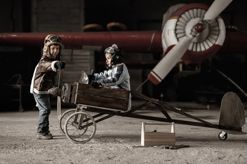 Young Aviators in a aircraft in a hangar with these planes