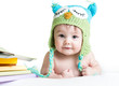 baby in funny knitted hat owl with books  on white background