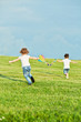 Little girl and boy run on meadow to fly kite, rear view