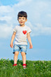 Little boy in shorts and white t-shirt with pinned red heart