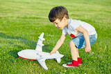 Little boy plays with inflatable model of airplane