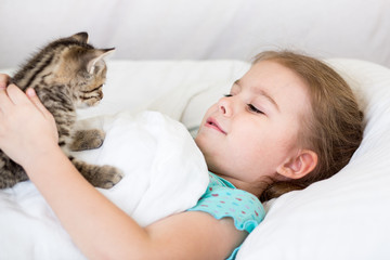 Child girl with kitten laying in the bed