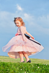Little girl dressed in light-rose gown turns on grassy meadow