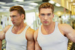 Young man bodybuilder stands leaning to mirror in gym hall