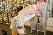 Athletic strong bodybuilder execute exercise in sport gym hall