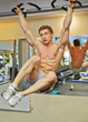 Bodybuilder does lateral and abdominal exercises hanging