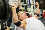 Athlete man does bench press exercise in gym hall