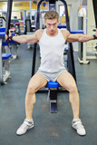 Bodybuilder does shoulders exercises in gym hall