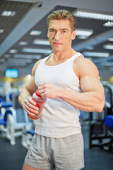 Portrait of young athlete man who stands in fitness hall