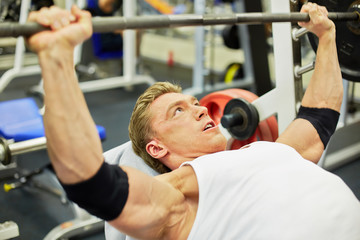 Young athlete man does bench press from chest exercise