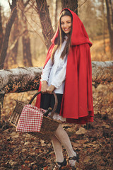 Happy little red riding hood poses in the forest