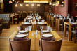 Roomy hall in restaurant with wooden furniture