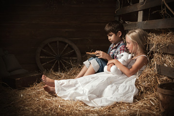 Children reading the book on the hay in the barn