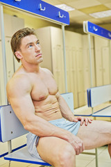 Bodybuilder sits tired leaning back on bench in locker room